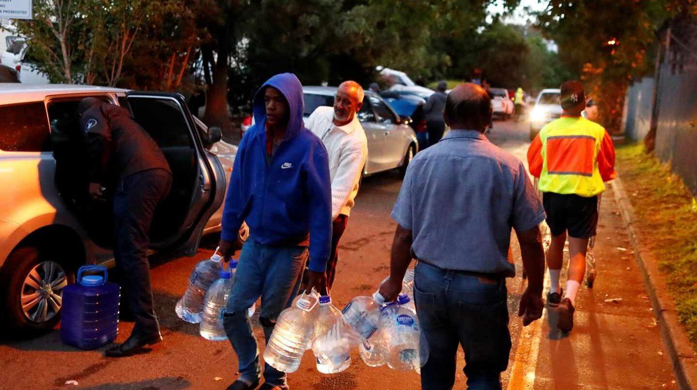 Los habitantes de Ciudad del Cabo, cargados de garrafas, acuden a los puntos de abastecimiento de agua repartidos por la ciudad.