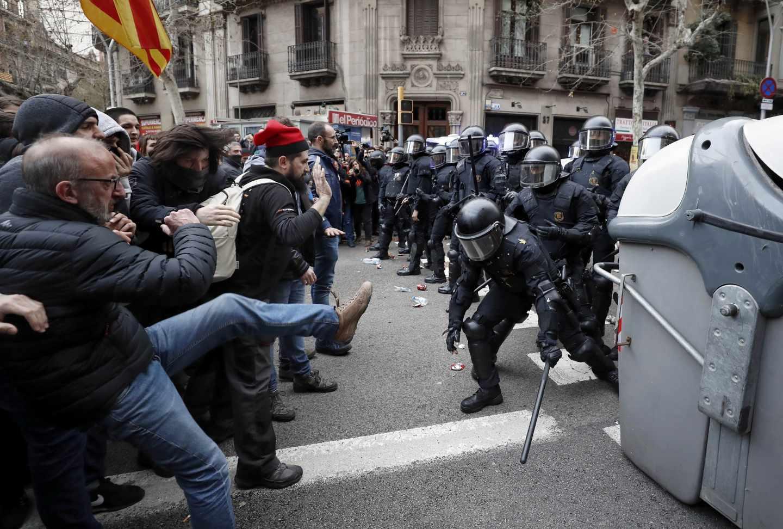 Miembros de los Mossos d´Esquadra impiden el paso de manifestantes en las inmediaciones de la Delegación del Gobierno en Cataluña, donde centenares de independentistas tratan de desbordar el cordón policial en protesta por la detención del expresidente catalán Carles Puigdemont.