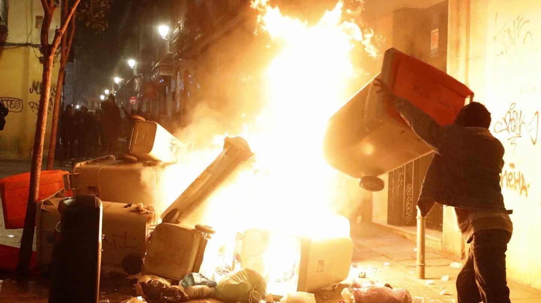 Un joven lanza contenedores al fuego en la noche del pasado jueves en el barrio de Lavapiés.