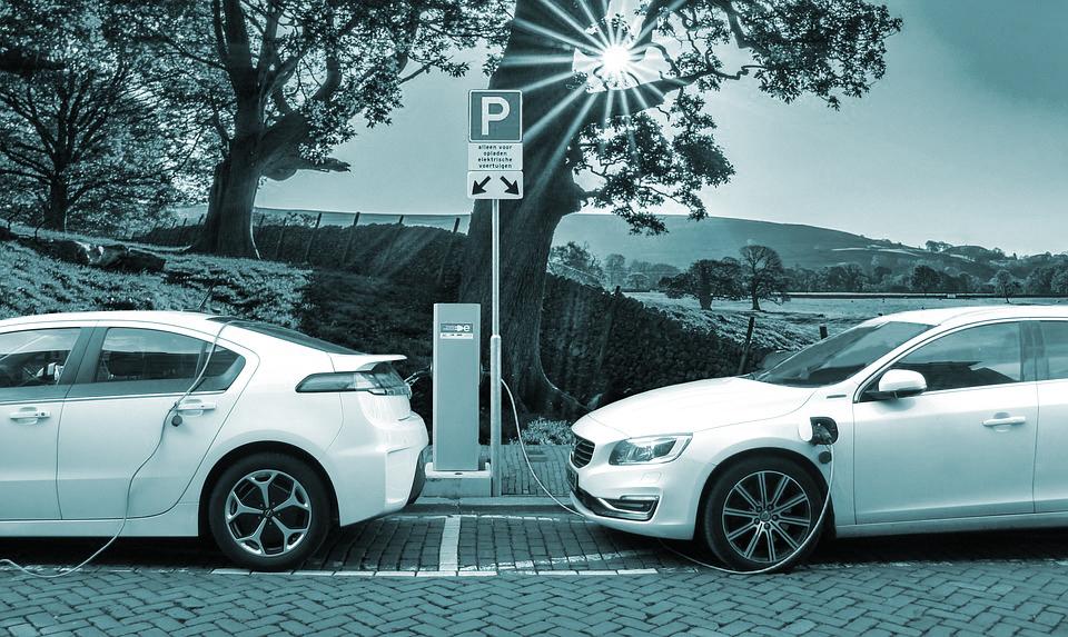 Dos vehículos eléctricos repostan en una estación de servicio.