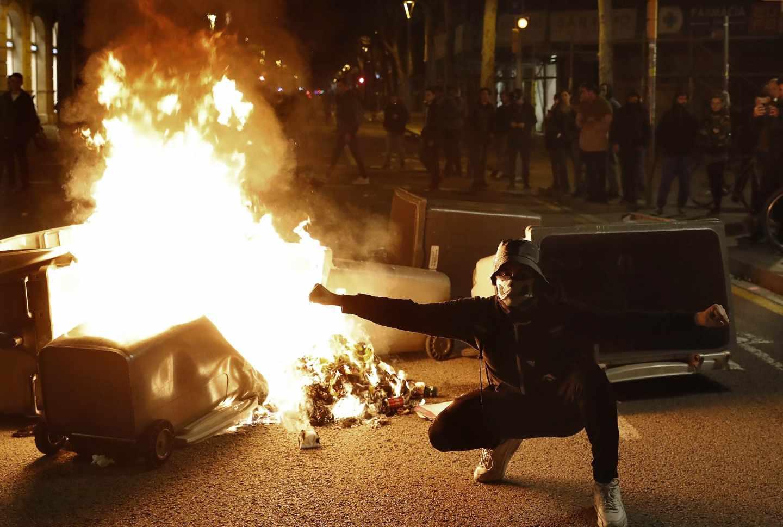 Un manifestante, junto a uno de los contenedores incendiados en Barcelona durante los disturbios del 25 de marzo.