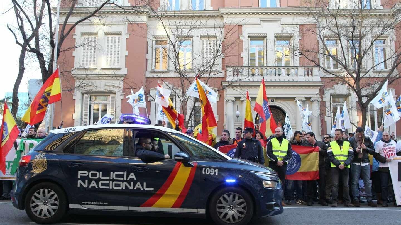 Un patrullero de la Policía Nacional pasa junto a una concentración en demanda de la equiparación salarial.