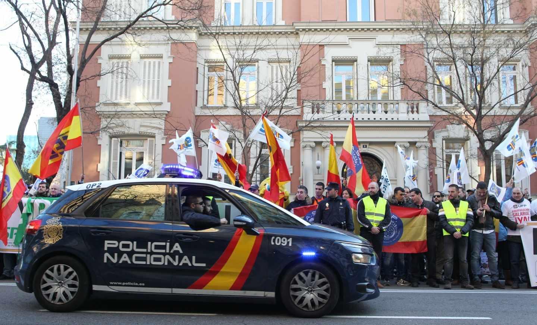 Un patrullero de la Policía Nacional pasa junto a una concentración en vísperas de que se firmase el acuerdo de equiparación salarial.