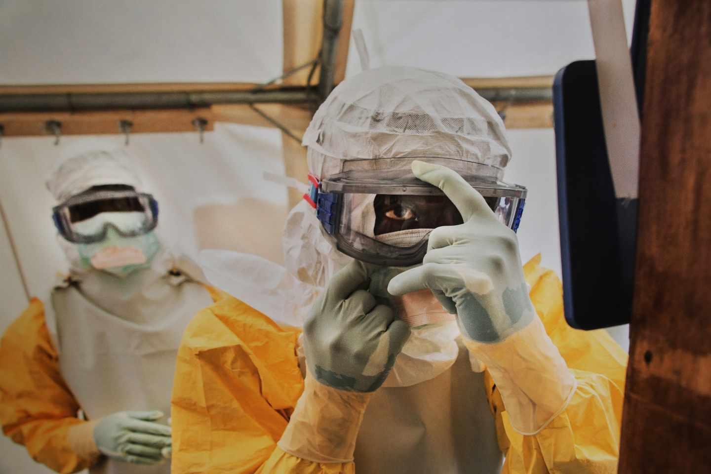 Voluntarios se colocan frente al espejo el traje de protección de enfermedades altamente contagiosas.