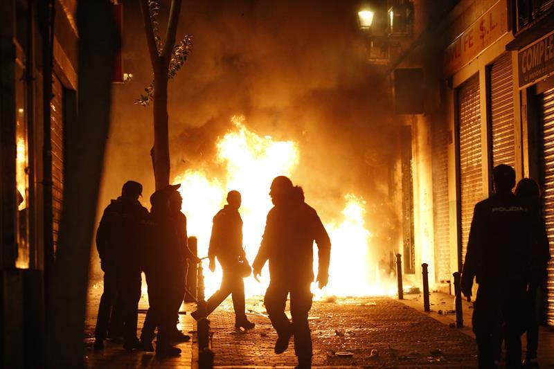 Violentos incendian mobiliario urbano en la noche de este jueves en el barrio madrileño de Lavapiés.