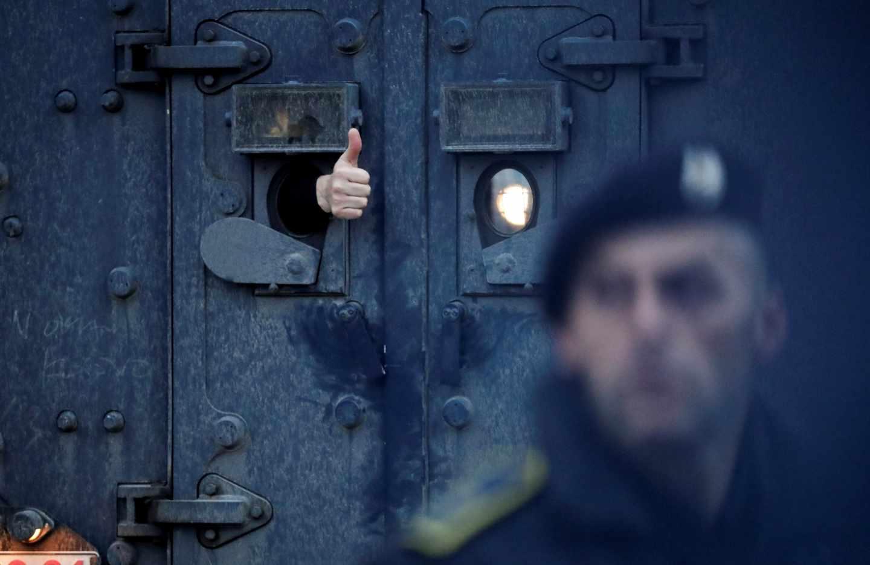 El delegado del gobierno de Serbia para Kosovo, Marko Djuric, gesticula desde el interior del vehículo militar que le trasladaba tras su detención en Mitrovica.