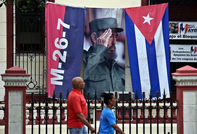 Dos cubanos ante una imagen del fallecido líder Fidel Castro, en La Habana.