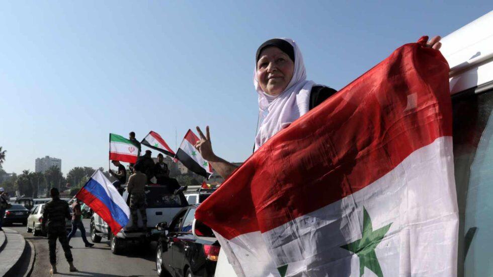 Una mujer siria sujeta una bandera en Damasco.