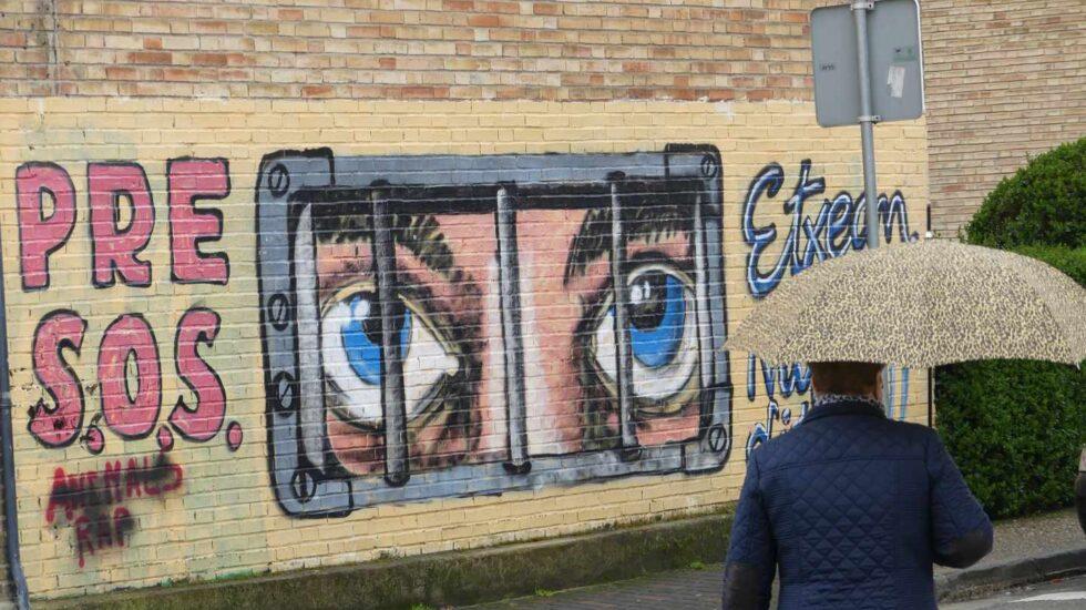Una mujer pasa frente a un mural de apoyo a los presos de ETA en Alsasua.