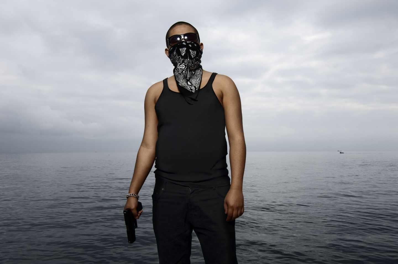 Joven latino posando con pistola en la Barceloneta