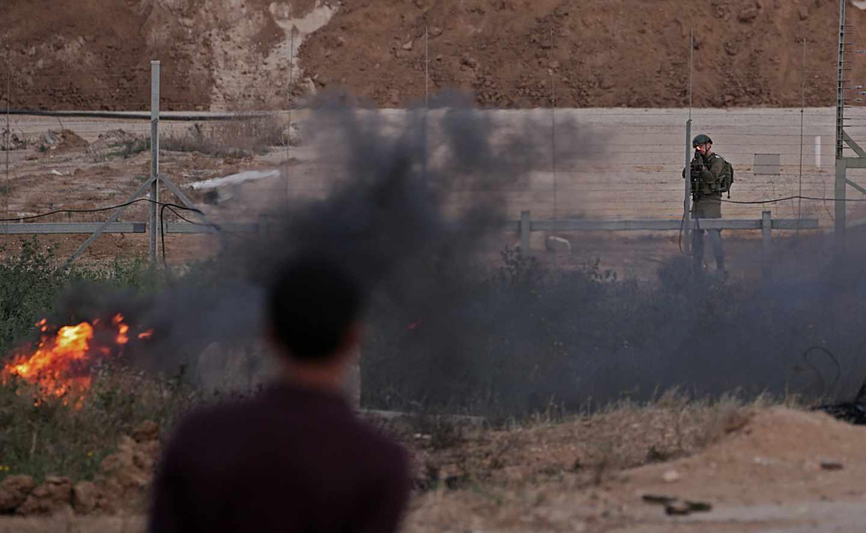 Un soldado israelí apunta a los manifestantes palestinos hoy, martes 3 de abril de 2018, durante los enfrentamientos con las tropas israelíes a lo largo de la frontera entre Israel y la Franja de Gaza, en el este de la Franja de Gaza. Los manifestantes planean reclamar el derecho de los refugiados palestinos en Medio Oriente a regresar a los hogares de los que huyeron en la guerra que rodeó la creación de Israel en 1948. EFE