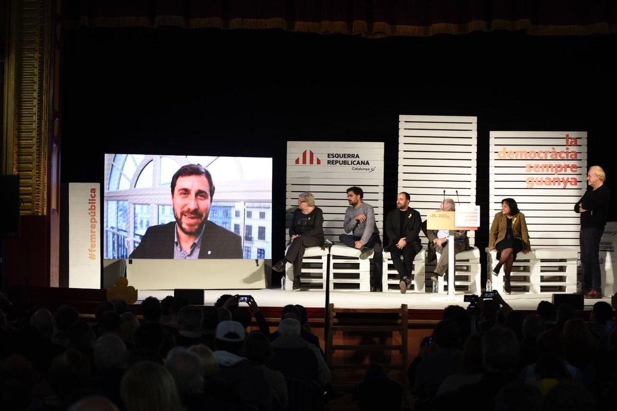 El diputado de ERC Toni Comín interviene en vídeo durante un mitin en campaña electoral.