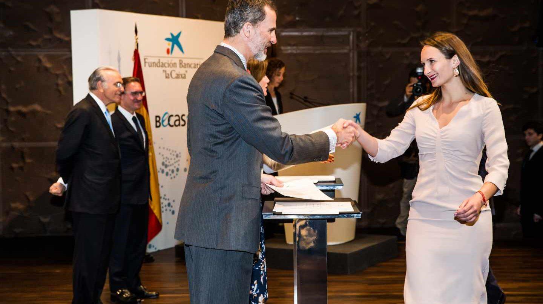 El rey Felipe VI saluda a una de las estudiantes becadas por la Fundación La Caixa.