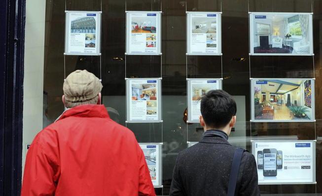 Dos viandantes observan anuncios de alquiler y venta de casas en una inmobiliaria.