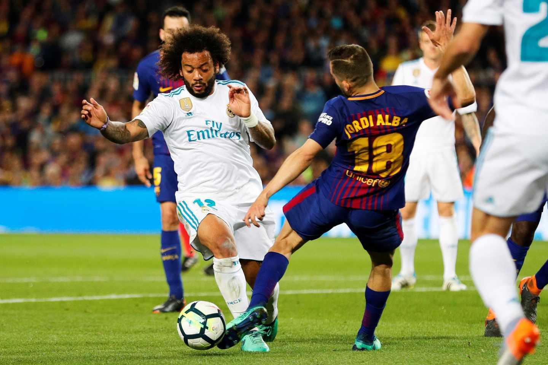 El defensa brasileño del Real Madrid, Marcelo (i), intenta superar la entrada del jugador del FC Barcelona, Jordi Alba, durante el encuentro correspondiente a la jornada 36 de primera división que disputan esta noche en el estadio del Nou Camp.