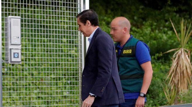 Eduardo Zaplana, trasladado a los calabozos por un agente de la UCO de la Guardia Civil.