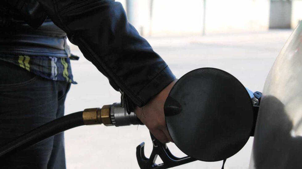 Un conductor llena el depósito de su coche en una gasolinera.