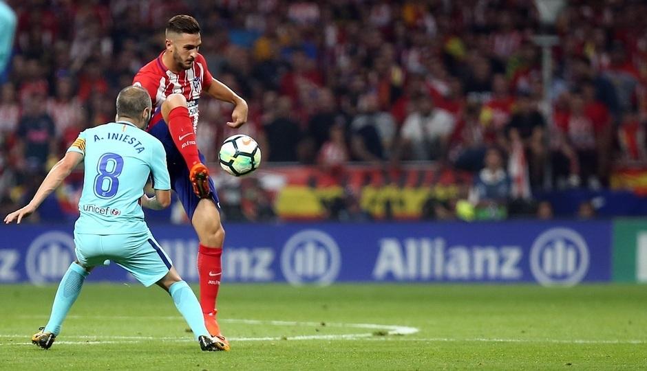 Koke e Iniesta disputan un balón en un partido de Liga.