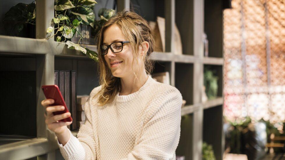 Una chica mira el móvil y sonríe.