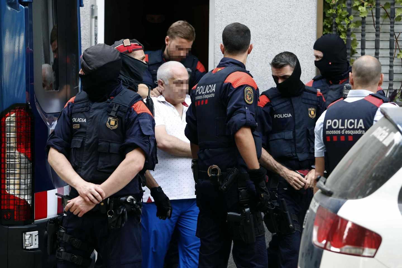 Los Mossos d'Esquadra trasladan a un detenido.
