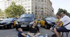 Un grupo de taxistas corta la Gran Vía de Barcelona.
