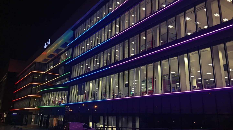 Sede de Axa iluminada con la bandera del arco iris.