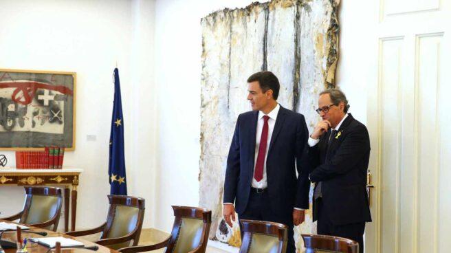 El presidente del Gobierno español, Pedro Sánchez (i), muestra al presidente de la Generalitat, Quim Torra (d), el salón y la mesa del Consejo de Ministros tras la reunión mantenida hoy en el Palacio de la Moncloa