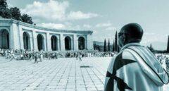 Un hombre ataviado con una capa blanca y la característica cruz roja de los caballeros del Temple observa la concentración celebrada hoy en el Valle de los Caídos, para protestar contra la intención del Gobierno de Pedro Sánchez de exhumar los restos del dictador Francisco Franco, a la que instó el pasado mes de mayo en una votación el Congreso.