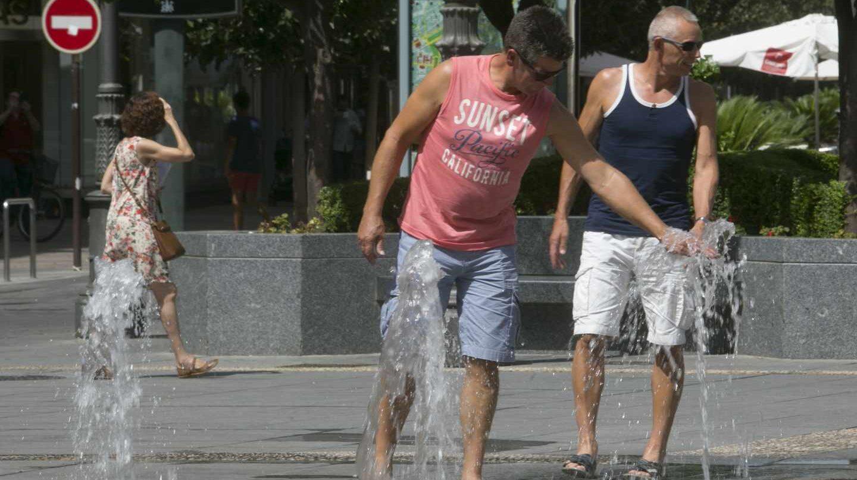 Hombre sofocando el calor en una fuente pública
