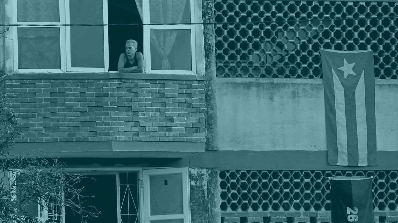 Una persona se asoma a la ventana en un edificio adornado con la bandera cubana.