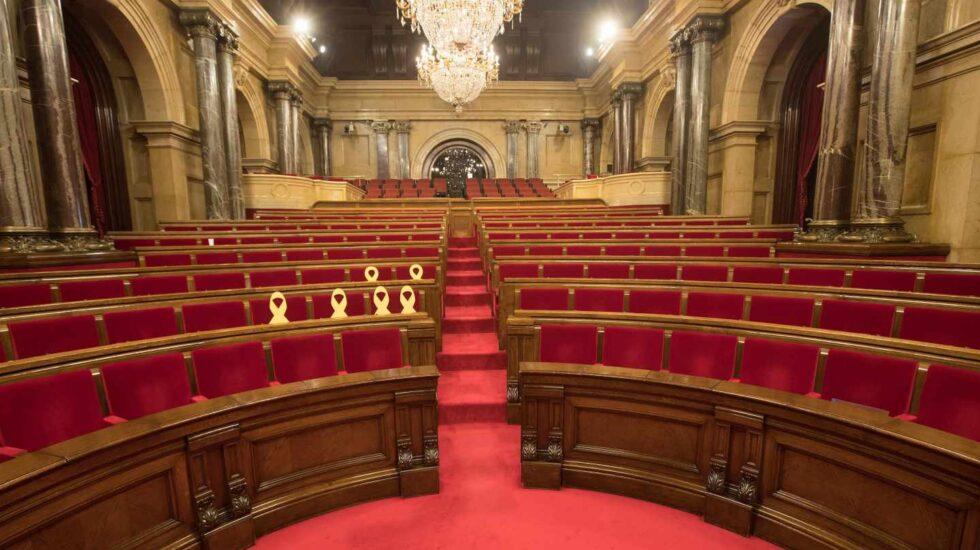 El Parlament de Cataluña, vacío y con los lazos amarillos en los escaños de los diputados huidos y encarcelados.
