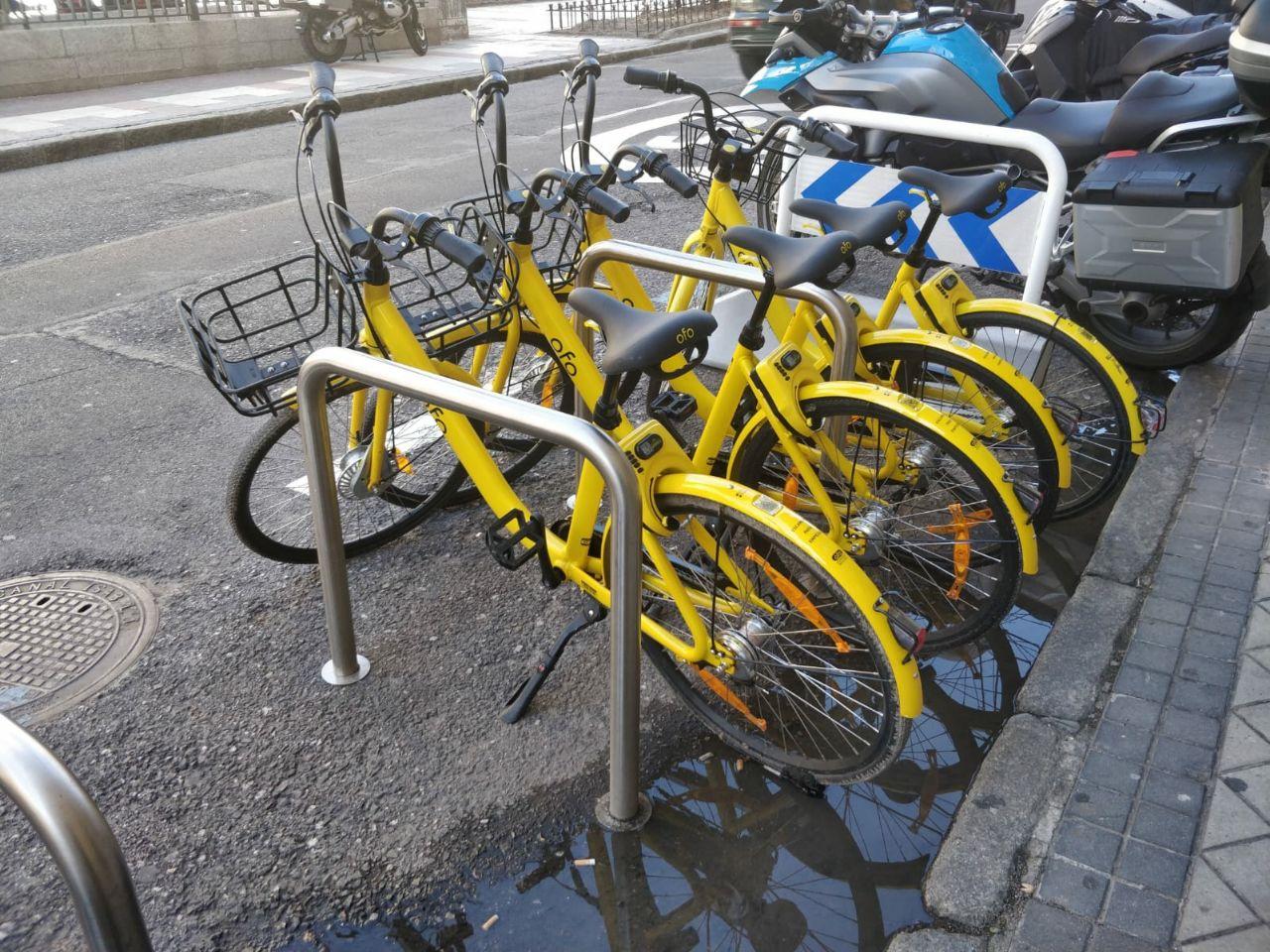 Varias bicicletas de Ofo Bike en un aparcabicis.