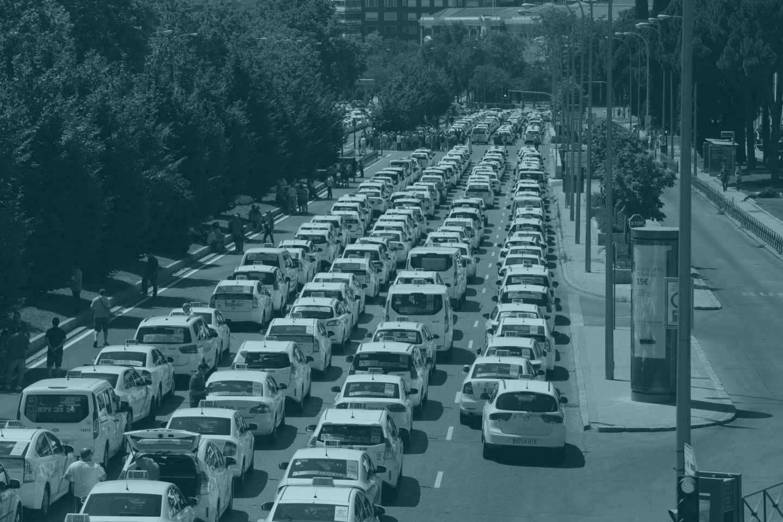 Un grupo de taxis permanecen concentrados a su paso por el ministerio de Fomento, en Madrid.