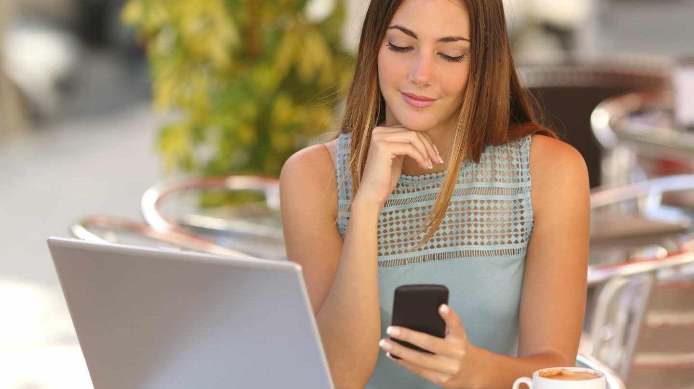 Una chica mirando su teléfono móvil.
