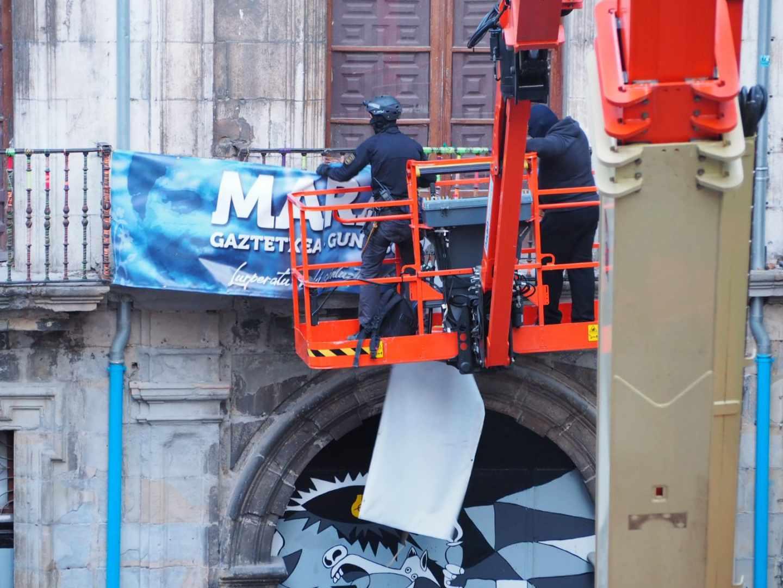 Momento en el que agentes de policía retiran la pancarta del Gaztetxe Maravillas.