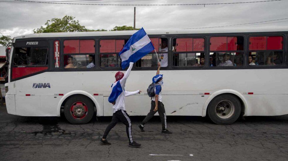 Dos jóvenes con las caras tapadas y una bandera de Nicaragua caminan frente a un vehículo de transporte público durante una protesta por 6 por el ciento del presupuesto nacional a las universidades, y la autonomía en las mismas hoy, jueves 2 de agosto de 2018, en el día numero 107 de protestas contra el gobierno de Daniel Ortega, frente a la Universidad Centroamericana (UCA), en Managua (Nicaragua). Los alumnos de la UCA, quienes habían organizado un plantón para este jueves para reclamar los fondos de ley que el Gobierno había negado al centro de estudios superiores, siguieron adelante con la protesta, pese a que la pasada noche, el Ejecutivo informó de que en el mes de agosto realizará el desembolso correspondiente.