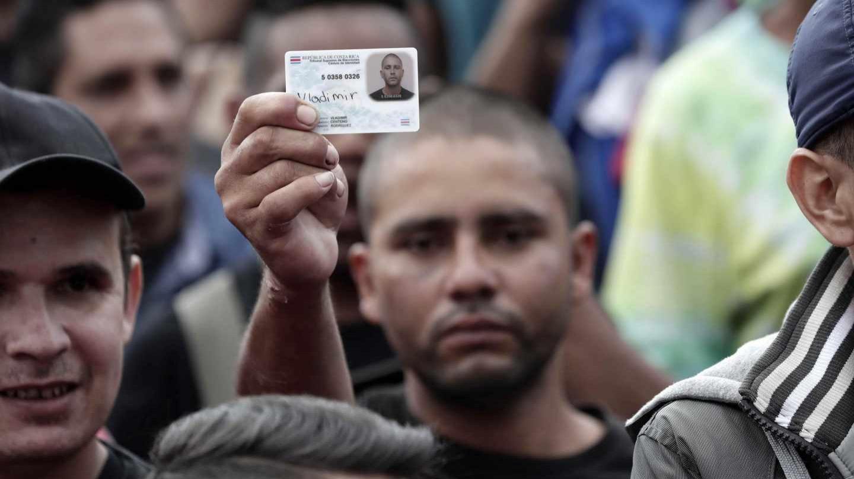 Un hombre muestra su cédula de identidad como protesta junto a cientos de costarricenses