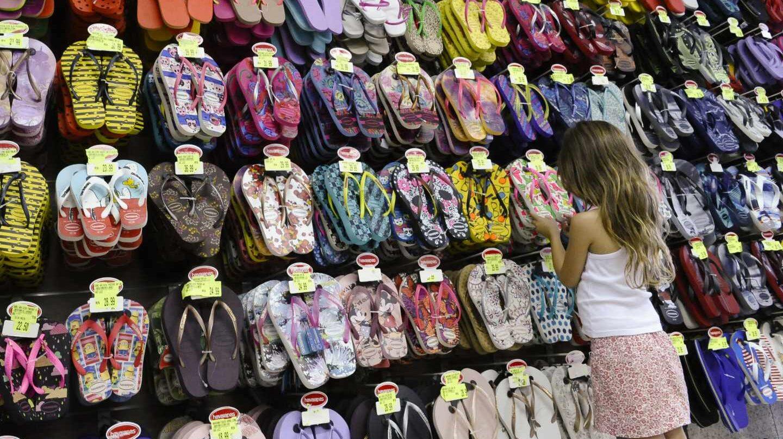 Una niña mirando sandalias en una tienda