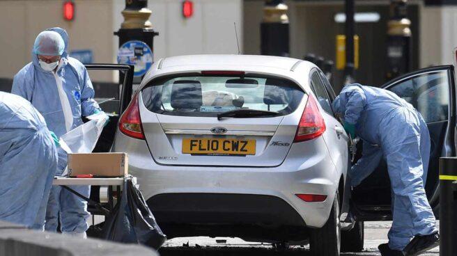 Oficiales forenses examinan el coche que chocó contra las barreras del Parlamento.