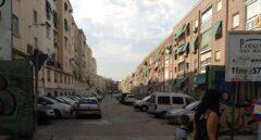 Una mujer y su hijo pasan junto a la calle fantasma del Barrio de La Elipa, hoy convertida en aparcamiento.
