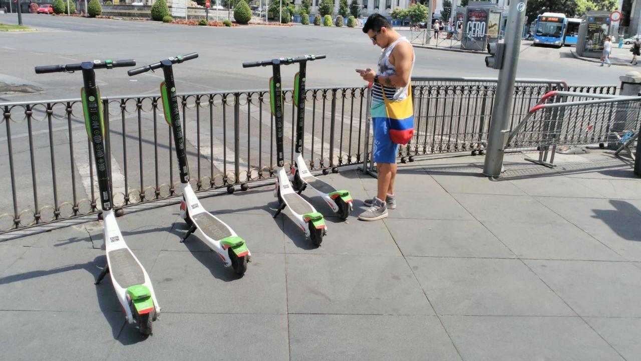 Un usuario desbloquea uno de los patinetes de Uber en el centro de Madrid.