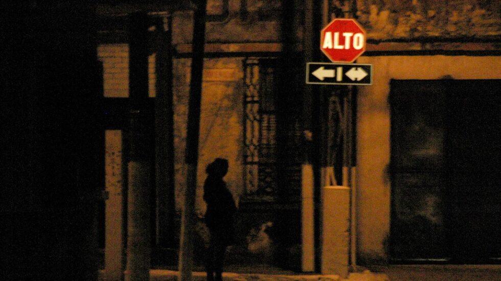 Prostituta de noche en una esquina.