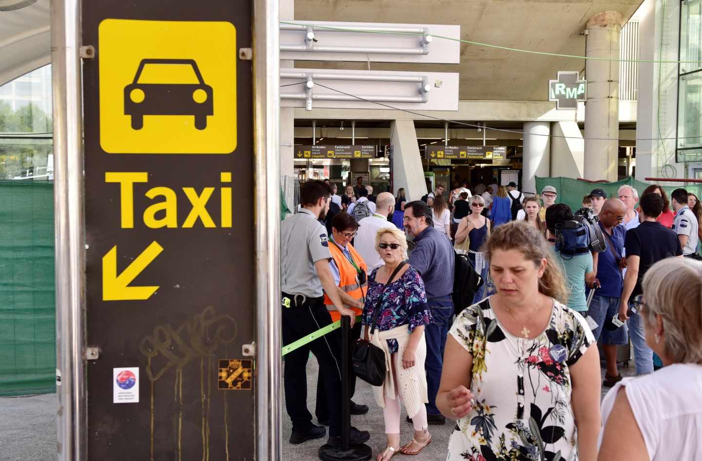 Varios turistas esperan en la cola del Aeropuerto de Palma para coger un taxi.