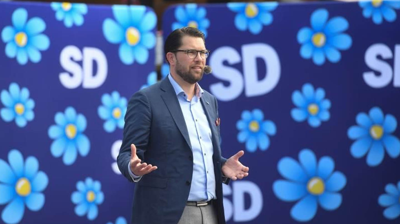 Jimmie Akesson, líder de los Demócratas de Suecia, en un mitin con la flor con los colores de la bandea sueca de fondo.