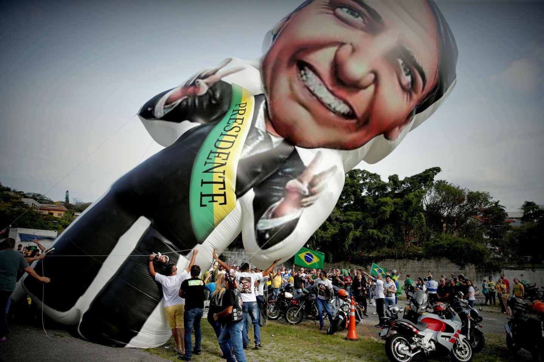 Seguidores del candidato ultraderechista brasileño Jair Bolsonaro elevan un globo con su imagen.