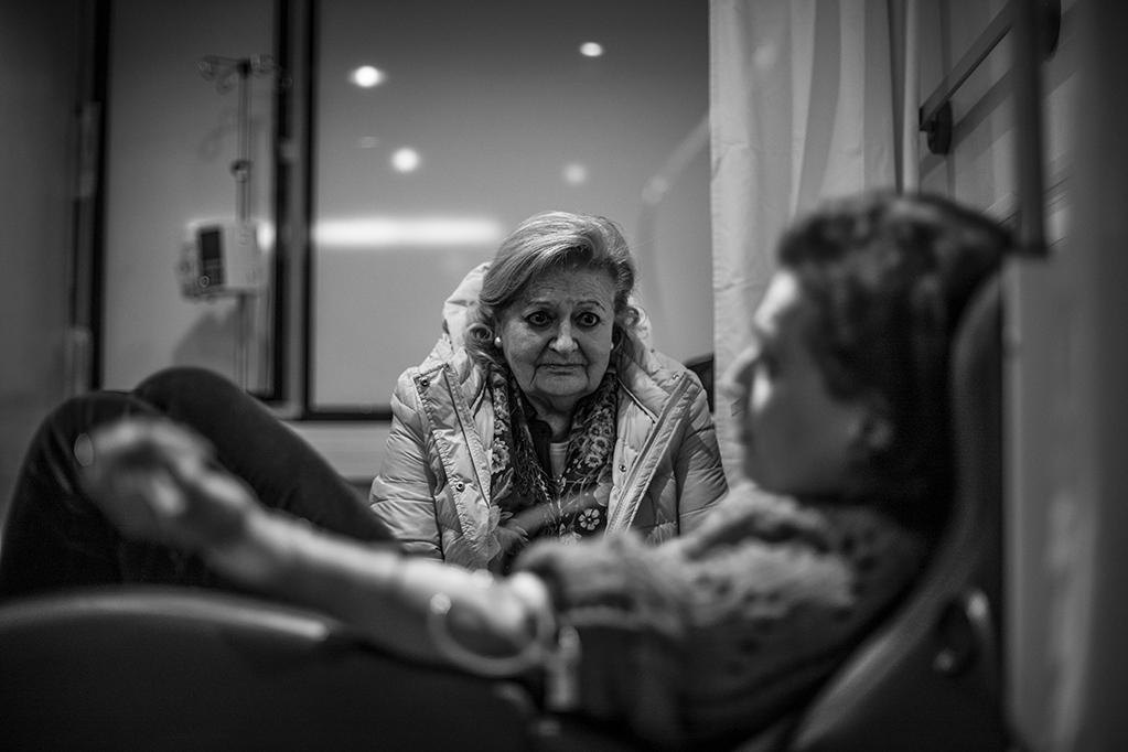La madre de Piedad, vigila a su hija dormida mientras recibe quimioterapia en el Hospital Universitario Reina Sofia, Murcia, España, Diciembre 2017.