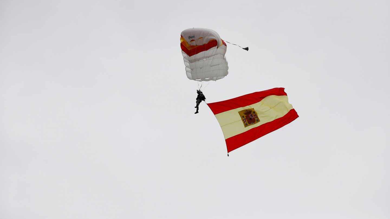 Un paracaidista desciende al inicio del desfile de la Fiesta Nacional.