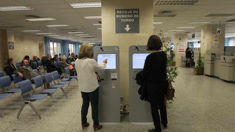 Dos mujeres piden turno en una oficina de la Agencia Tributaria.