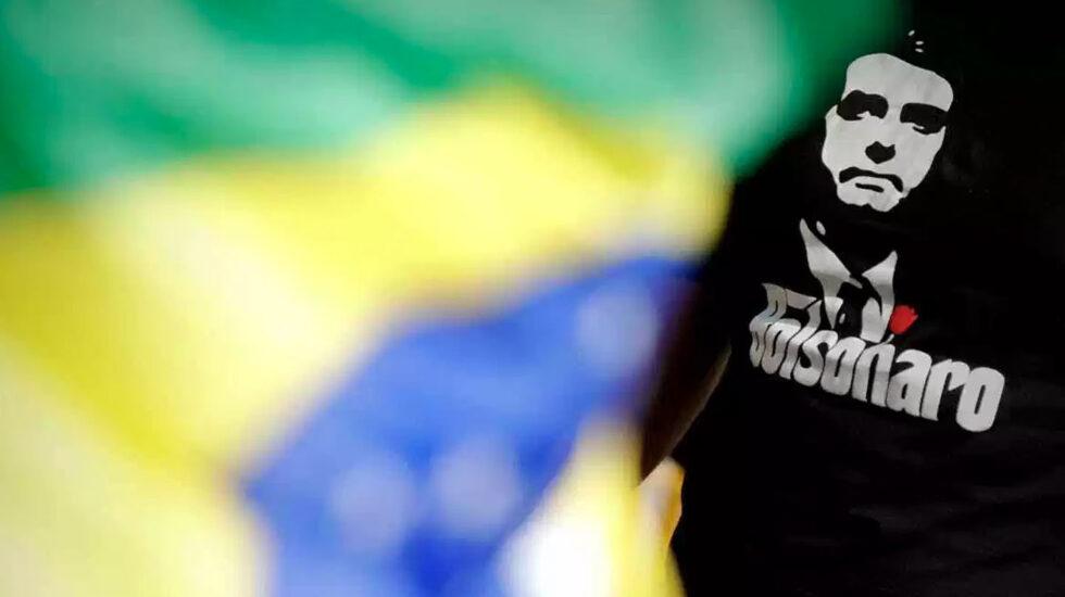 Un seguidor de Bolsonaro muestra el rostro de su ídolo en la camiseta con los colores de la bandera de fondo.