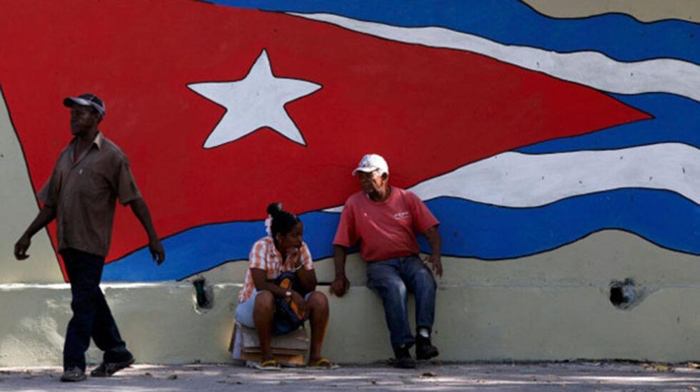 Dos cubanos se toman un respiro ante una bandera gigante en La Habana.